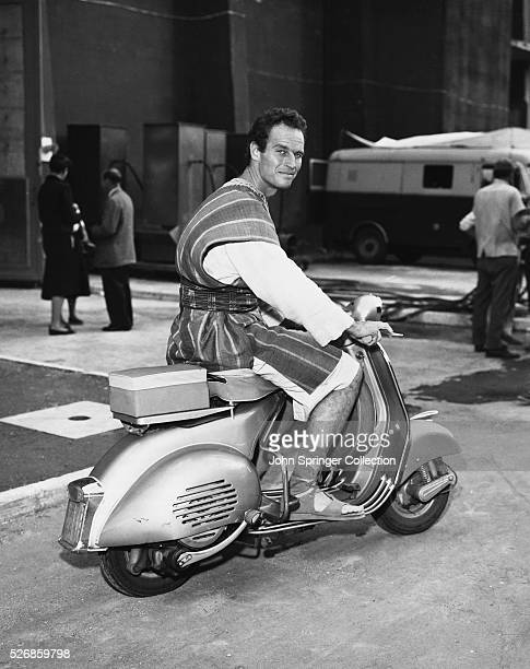 Actor Charlton Heston takes a break from the filming of BenHur by riding a moped to clear his head
