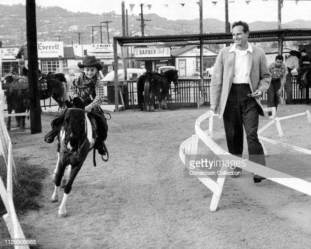 Actor Charlton Heston while his son Fraser Clarke Heston rides a minihorse in circa 1959