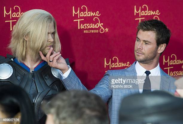 Actor Chris Hemsworth takes a close look at a figure of himself in character as Thor at the premiere of Marvel's Avengers Age Of Ultron at the Dolby...