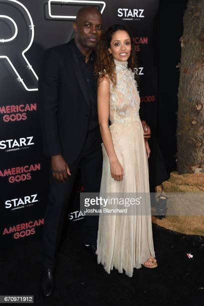 """Actor Chris Obi and guest arrive at the Premiere of """"American Gods"""" on April 20, 2017 in Los Angeles, California."""