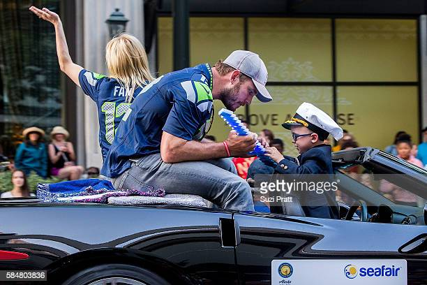 Actor Chris Pratt and son Jack Pratt ride in the Seafair Torchlight Parade Grand Marshal vehicle on July 30 2016 in Seattle Washington