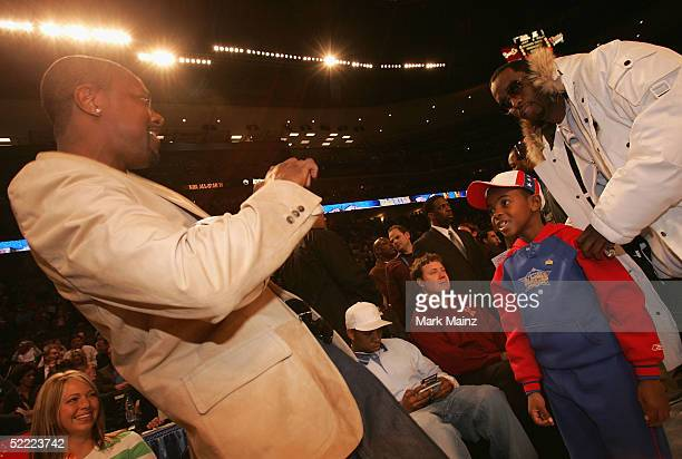 Actor Chris Tucker takes a picture of his son with Sean 'P Diddy' Combs at the 2005 NBA All Star Game at the Pepsi Center on February 20 2005 in...