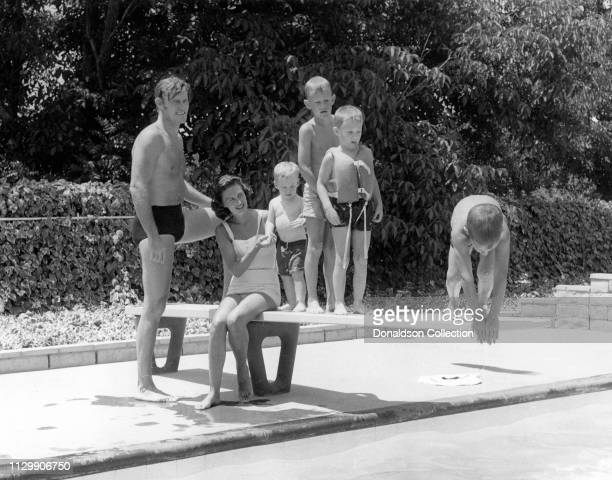 Actor Chuck Connors by the pool with his wife Elizabeth Jane Riddell Connors and their four sons Michael Connors Jeffrey Connors Stephen Connors and...