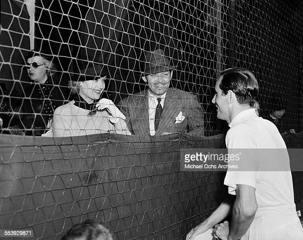 Actor Clark Gable and wife actress Carole Lombard talk with Bill Tildon during an event in Los Angeles California