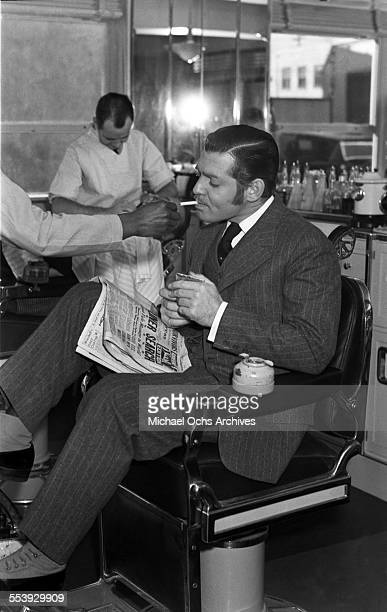 Actor Clark Gable has his cigarette lit as he gets his shoes shined in Los Angeles California