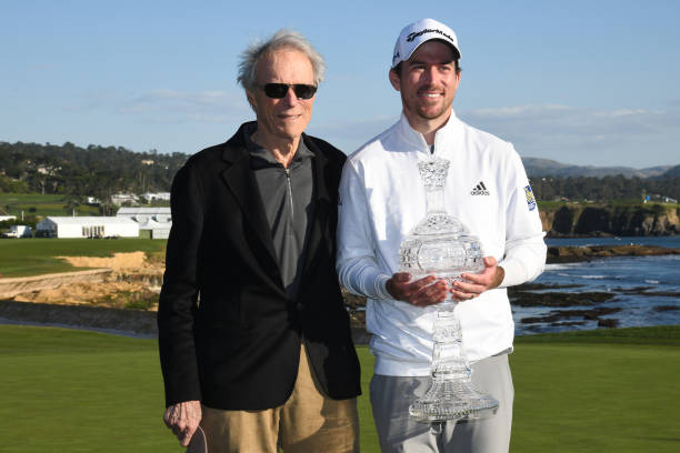 Actor Clint Eastwood and Nick Taylor of Canada pose with the trophy after Taylor won the ATT Pebble Beach ProAm at Pebble Beach Golf Links on...
