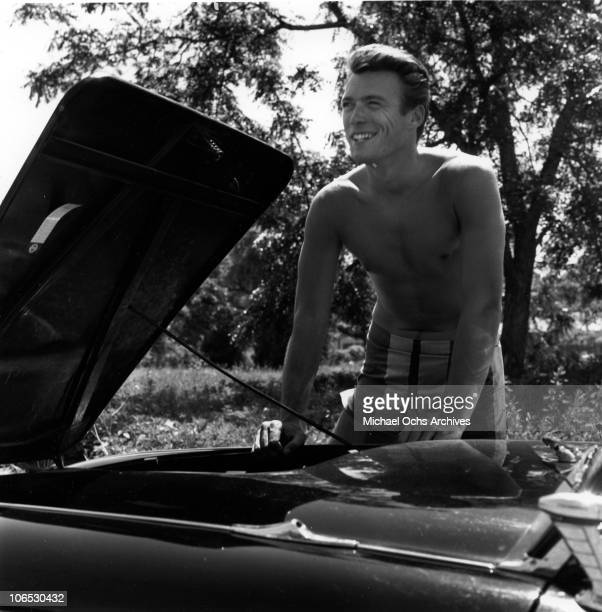 Actor Clint Eastwood checks under the hood of his car with his shirt off on June 5 1956 in Los Angeles California