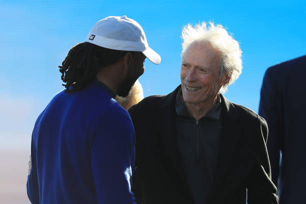 Actor Clint Eastwood talks with Larry Fitzgerald of the Arizona Cardinals after the final round of the ATT Pebble Beach ProAm at Pebble Beach Golf...