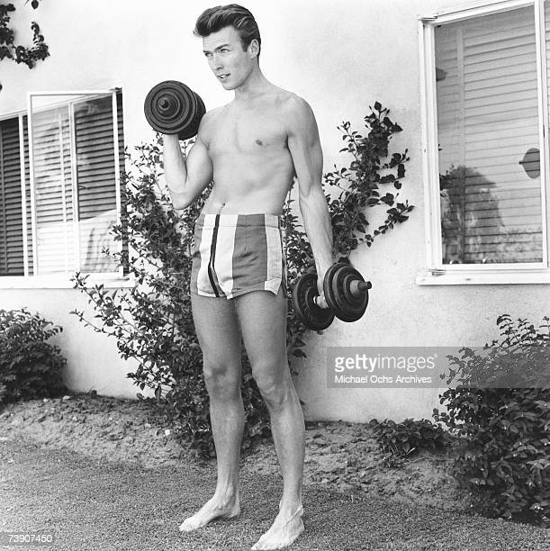 Actor Clint Eastwood works out with dumbbells at home on June 1 1956 in Los Angeles California