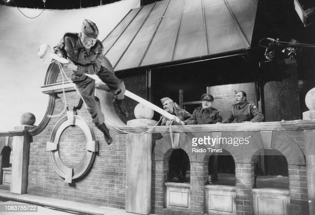 Actor Clive Dunn climbing a flag pole watched by John Le Mesurier Arthur Lowe and James Beck in a scene from the episode 'Battle of the Giants' of...