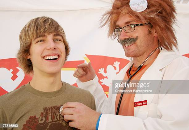 Actor Cody Linley and Dr Funny Bone pose at the Operation Rescue Kit game Mobile Rescue Unit booth at the State Fair of Texas at Fair Park on October...