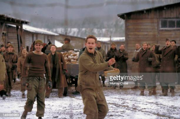 Actor Cole Hauser throwing bread to Russian prisonersofwar in a scene from the film 'Hart's War' 2002