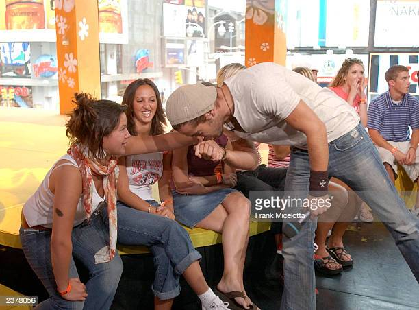 Actor Colin Farrell one of the stars of the new film 'SWAT' kisses the hand of a fan on MTV TRL at the MTV Times Square Studios August 7 2003 in New...