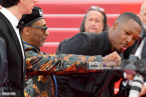 Actor Corey Hawkins looks at the hands of director Spike Lee wearing knuckle rings with love and hate on them as he attends the screening of...
