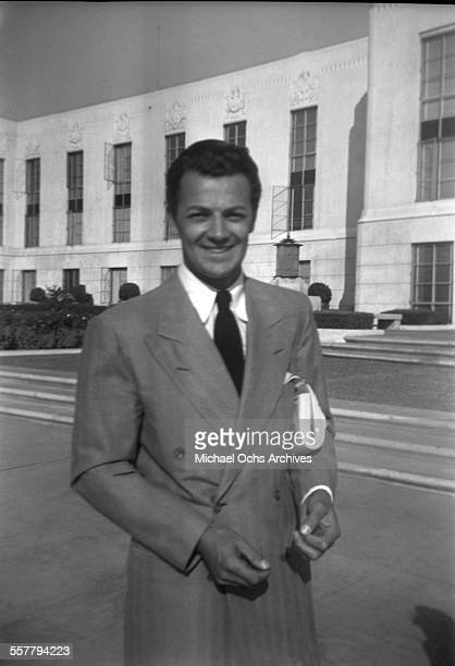 Actor Cornel Wilde poses at MGM studio in front of the Thalberg building in Los Angeles California