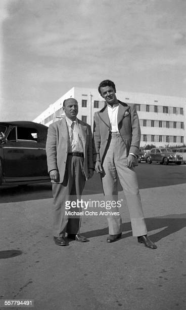 Actor Cornel Wilde poses with a friend in a parking lot in Los Angeles California
