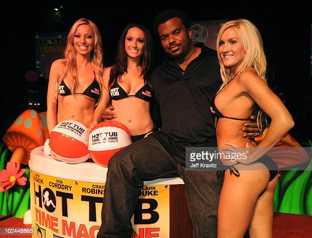 Actor Craig Robinson poses with models as he arrives at the Hot Tub Time Machine Bluray and DVD launch party at the Kandyland V red carpet at the...