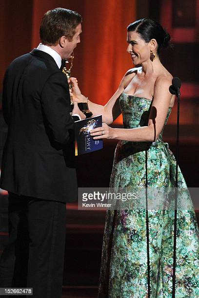 Actor Damian Lewis accepts Outstanding Lead Actor in a Drama Series award for 'Homeland' from actress Julianna Margulies onstage during the 64th...