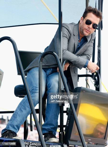 Actor Dane Cook sits in the pit box of Jimmie Johnson driver of the Lowe's Planes Chevrolet during the NASCAR Sprint Cup Series GoBowlingcom 400 at...