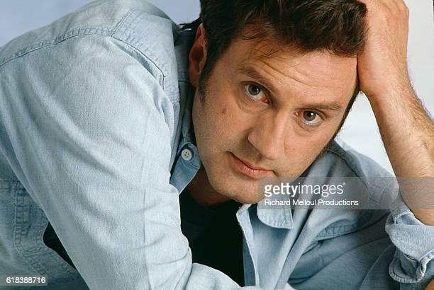 Actor Daniel Auteuil leans on his hand in Paris