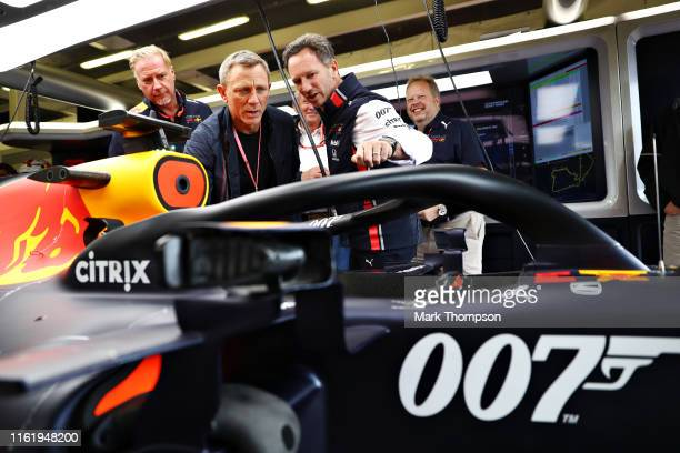Actor Daniel Craig gets a tour around the Red Bull Racing garage from Red Bull Racing Team Principal Christian Horner before the F1 Grand Prix of...