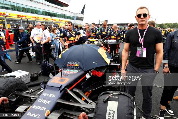 Actor Daniel Craig poses for a photo with the car of Pierre Gasly of France and Red Bull Racing on the grid before the F1 Grand Prix of Great Britain...