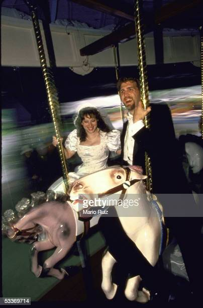 Actor Daniel Roebuck with bride Kelly Durst riding merrygoround at amusement park after their wedding