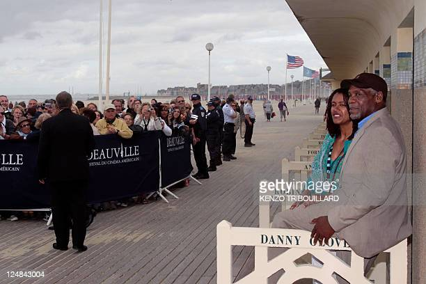 US actor Danny Glover and his wife Asake Bomani pose next to the beach closet dedicated to him on the Promenade des Planches in the French...