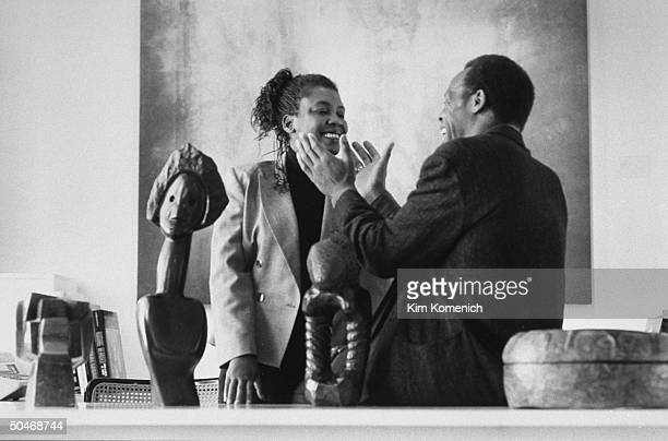 Actor Danny Glover chatting affectionately w his wife Asake Bomani at desk w African art objects on it at her yettobe completed Bomani Gallery