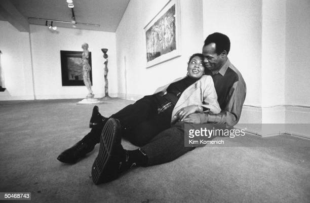 Actor Danny Glover cuddling w his wife Asake Bomani as they sit on floor in Allrich Gallery w paintings sculptures in the bkgrd