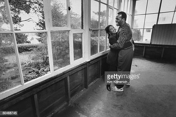 Actor Danny Glover hugging his wife Asake Bomani on large glassedin porch
