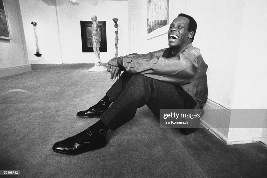Actor Danny Glover sitting on floor in Allrich Gallery.
