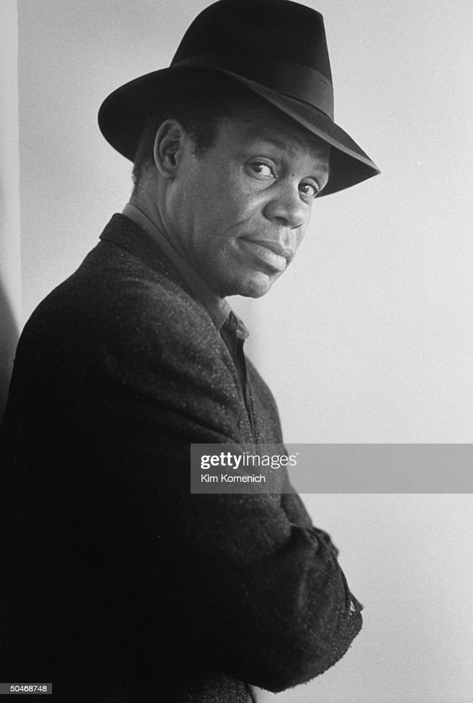 Actor Danny Glover wearing hat as he leans against the wall in Allrich Gallery.