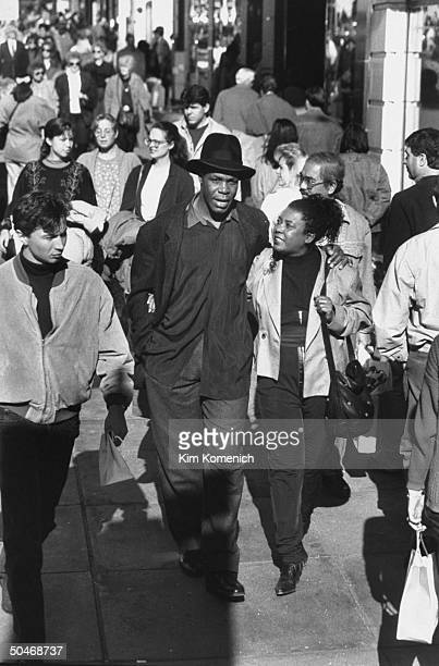 Actor Danny Glover wearing hat as he walks w his arm around wife Asake Bomani while strolling on crowded Stockton St