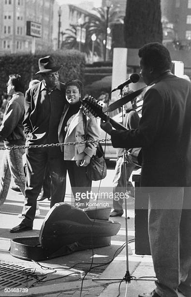 Actor Danny Glover wearing hat w his arm around wife Asake Bomani as they stand listening to man singing into a mike playing guitar on the street