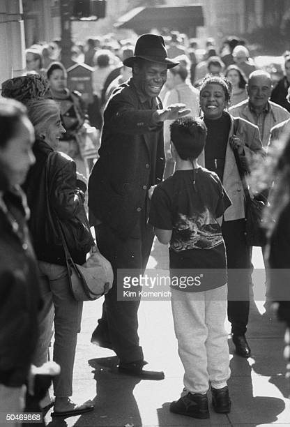 Actor Danny Glover wearing hat w his wife Asake Bomani greeting young fan while strolling on crowded Stockton St