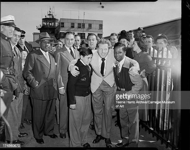 Actor Danny Kaye embracing two boys in front of crowd including Howard McKinney on left at Allegheny County Airport West Mifflin Pennsylvania October...