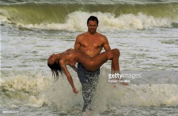 Actor Danny Quinn son of actor Anthony Quinn carries a nude woman out from the surf