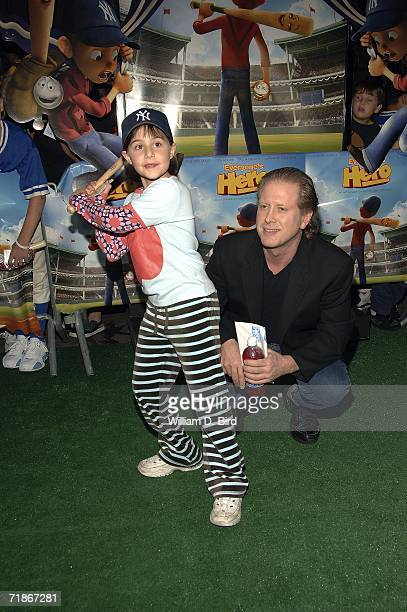 "Actor Darrell Hammond watches as his daughter Mia takes a swing with a baseball bat at the New York Premiere of ""Everyone's Hero"" at The AMC Loews..."