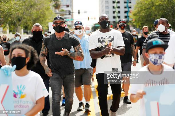 Actor Dave Bautista shares hand sanitizer with WWE wrestler Titus O'Neil during the Love Walk on June 27 2020 in downtown Tampa Florida Thaddeus...