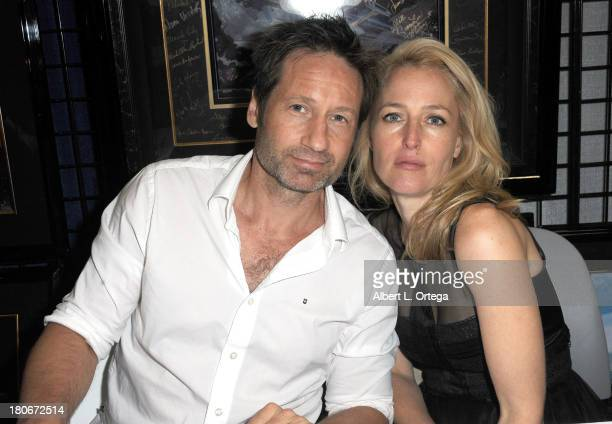 Actor David Duchovny and Gillian Anderson of 'The XFiles' sign autographs at the LightSpeed Booth on the convention floor on Day 1 of the 2013...