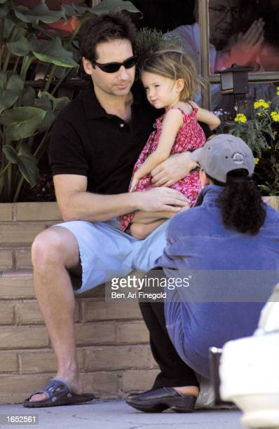 Actor David Duchovny dresses and comforts his daughter before having lunch at A Votre Saunte on November 20 2002 in Brentwood California