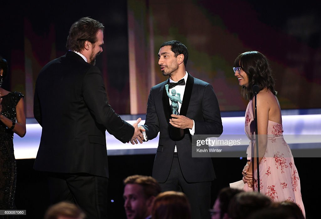 Actor David Harbour of 'Stranger Things' accepts Outstanding Performance by an Ensemble in a Drama Series from actors Riz Ahmed and Rashida Jones onstage during The 23rd Annual Screen Actors Guild Awards at The Shrine Auditorium on January 29, 2017 in Los Angeles, California. 26592_014
