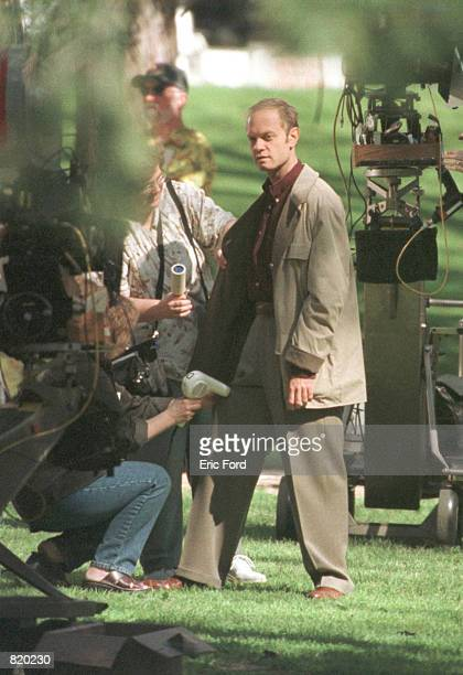 Actor David Hyde Pierce is cleaned up after Eddie the dog urinates on his leg while filming a scene for an episode of 'Frasier' being directed by...