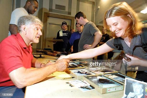 Actor David Prowse the man who played the physical role of Darth Vader in the film Star Wars greets a fan July 6 2001 at the Big Apple Comic Book Art...