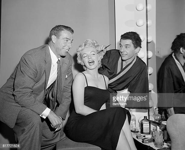 Actor David Wayne applies makeup to Marilyn Monroe while her husband Joe DiMaggio looks on The couple had been in the audience at the Martin Beck...