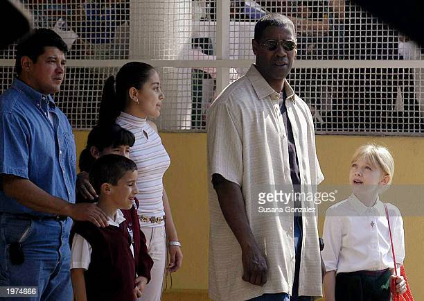 Actor Denzel Washington and actress Dakota Fanning stand beside some extras while filming a scene of Man On Fire at a sports club May 5 2003 in...