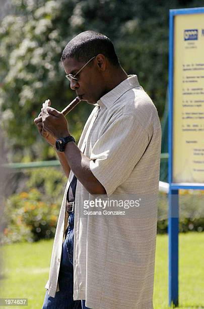 Actor Denzel Washington lights a cigar before filming a scene of Man On Fire at a sports club May 5 2003 in Mexico City Mexico