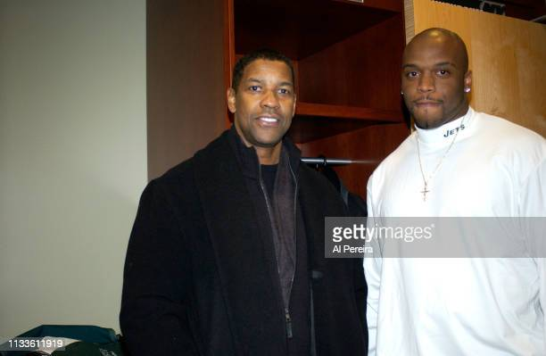 Actor Denzel Washington meets with New York Jets John Abraham in the locker room when he attends the New York Jets v Seattle Seahawks game at the...