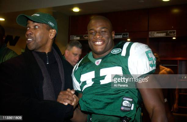 Actor Denzel Washington meets with New York Jets Linebacker Darrell McClover in the locker room when he attends the New York Jets v Seattle Seahawks...